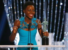 "Image: Lupita Nyong'o accepts the award for Outstanding Performance by a Female Actor in a Supporting Role for ""12 Years a Slave"" at the 20th annual Screen Actors Guild Awards in Los Angeles"